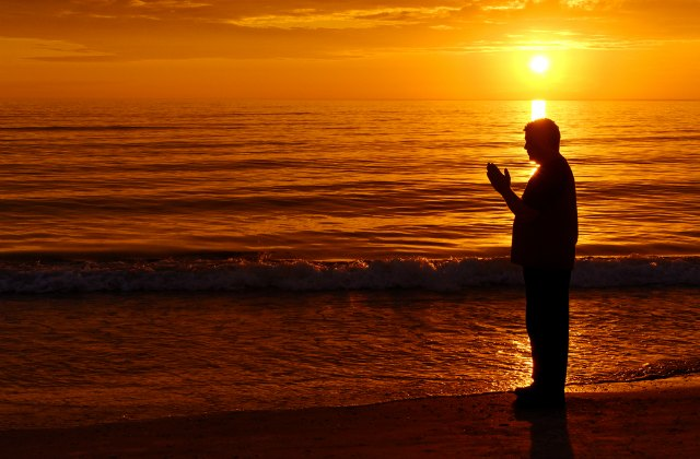 christian praying by the ocean