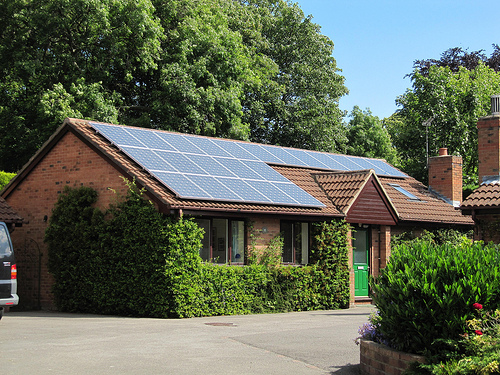 photo of a bungalow with solar panels on the roof