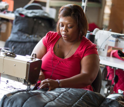 empowerment project worker sews coats for the homeless