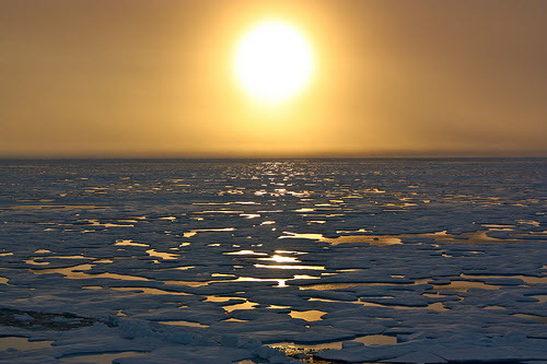 sunset over melting sea ice in the arctic